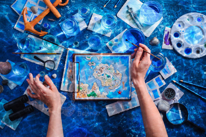 Overhead shot of an artist painting a fantasy island map. Underwater still life photography ideas