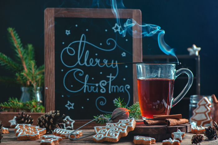 Hot tea, cookies and board with Christmas greetings